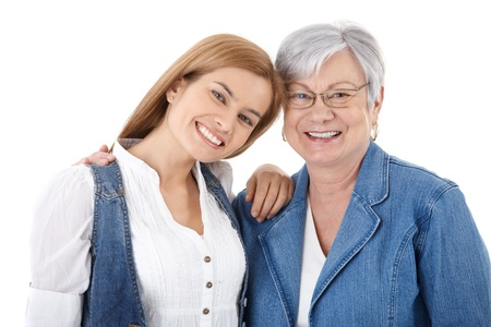 Portrait of happy young woman and senior mother smiling over white background.