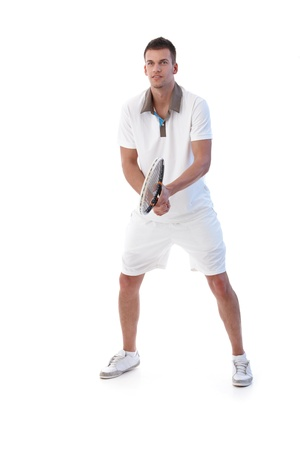 Young male tennis player waiting for ball, concentrating.