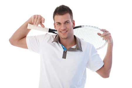 Young male tennis player taking a break, smiling, holding tennis racket.