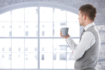 Casual man looking out of window, thinking, drinking tea.