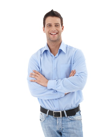 Laughing young businessman in casual clothing, standing with arms crossed, looking at camera.