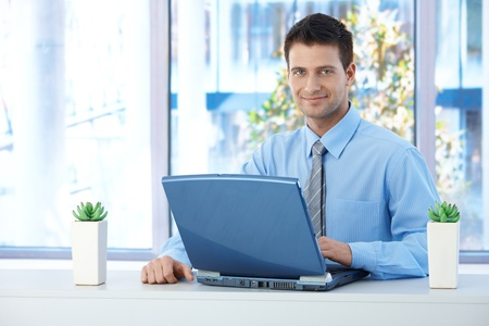 Smiling businessman working on laptop in office, looking at camera confidently.