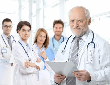 Portrait of aged male doctor teaching medical students.�