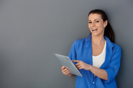 Laughing woman using touchscreen computer, pointing at screen, looking at camera.