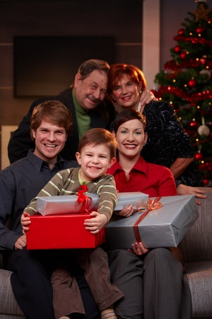 Portrait of happy family at christmas, sitting on sofa, holding presents, smiling.