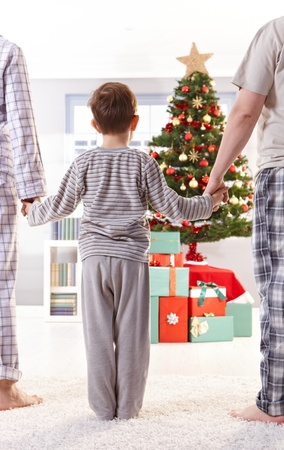 Family standing in pyjama holding hands on christmas morning.