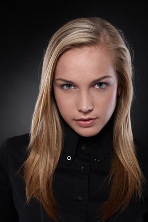 Studio portrait of unsmiling, blonde teenager in black, black background .