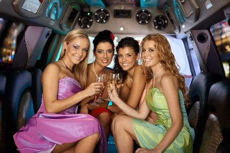 Group of beautiful elegant smiling girls celebrating in limousine.