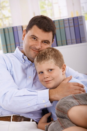 Portrait of father and ten year old boy, sitting on sofa, embracing, smiling.