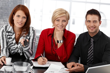 Portrait of smiling confident smart businesspeople at meeting, smiling at camera.