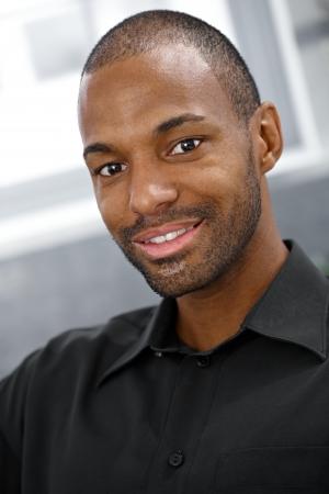 Closeup portrait of smiling goodlooking black man looking at camera.