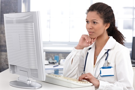 Afro-american female doctor sitting at desk working on computer.