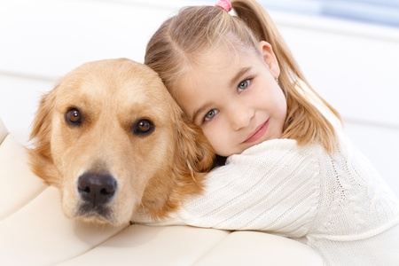 Cute little girl hugging golden retriever with love, looking at camera.
