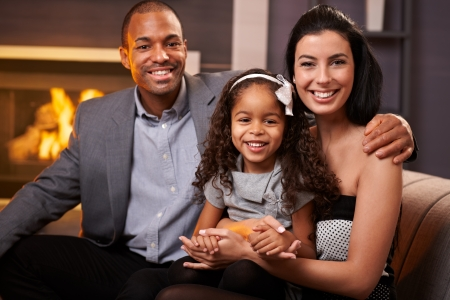Portrait of beautiful mixed race family at home by fireplace, all smiling, little girl in the middle.