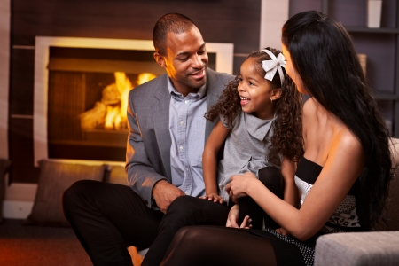 Happy ethnic family of three in living room by fireplace.