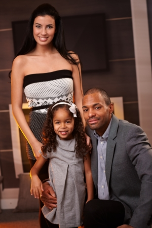Young mixed race couple and little daughter smiling at home.