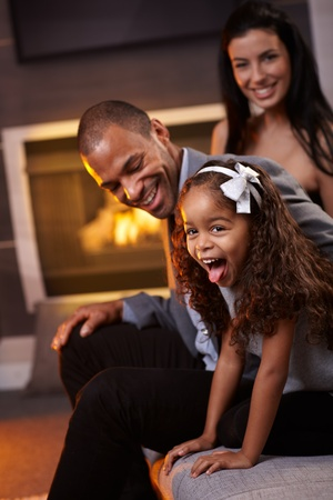 Beautiful diverse family having fun at home, little daughter sticking tongue, smiling.