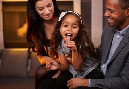 Attractive interracial family having fun at home, little girl sticking tongue.