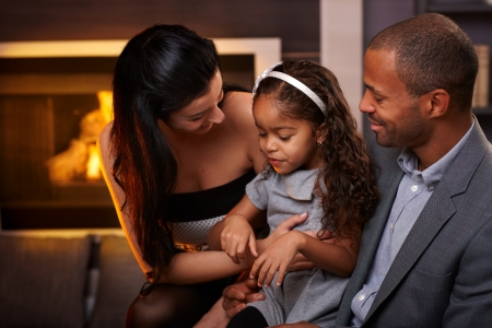 Beautiful loving family sitting in living room by fireplace, smiling.