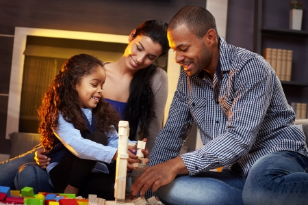 Happy interracial family of three playing together at home on floor, building tower by cubes.