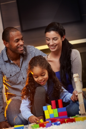 Happy interracial family sitting on floor at home, playing together, smiling.