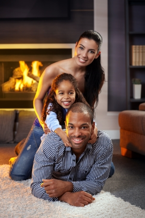 Portrait of happy diverse family at home lying on each other, smiling.