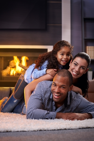 Happy interracial family having fun at home by fireplace, lying on each other's back, laughing.