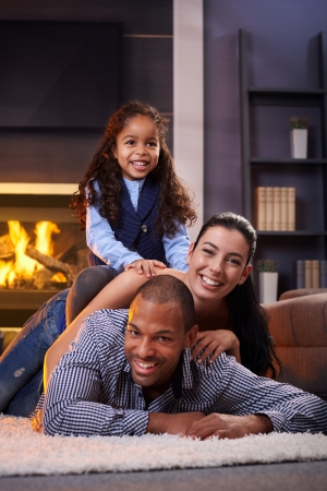 Happy diverse family having fun at home on floor, lying on each other.