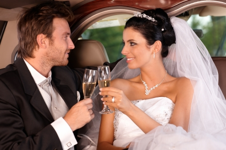 Bride and groom sitting in limousine, clinking glasses on wedding-day.