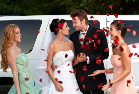 Photo pour Bridesmaids throwing rose petals on young couple. - image libre de droit