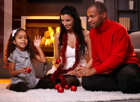 Beautiful diverse family at home in christmas time, sorting christmas decorations.