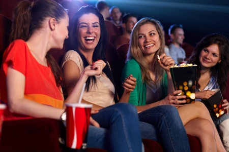 Photo for Happy girls sitting in multiplex movie theater, talking, laughing. - Royalty Free Image