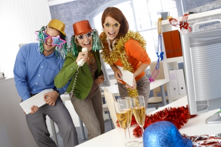 Funny new year eve party in office, businesspeople singing dancing with office tools, wearing festive party hat and glasses.