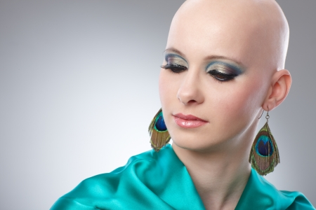 Beauty portrait of bald woman in turquoise silk dress  65533;