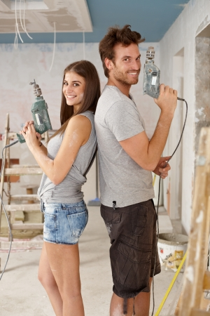 Happy young couple standing back to back holding power drill in renovated home.