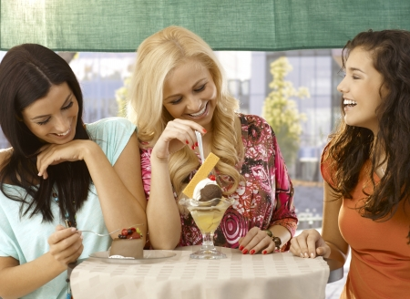 Happy female friends having cake and icecream at outdoor cafe, chatting, smiling.