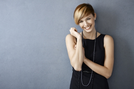 Photo pour Portrait of happy young woman in black dress and pearls on grey background - image libre de droit