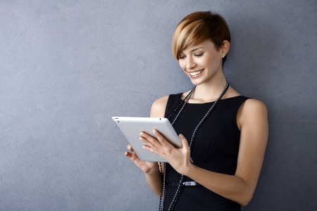Elegant young businesswoman using tablet leaning to wall, looking at screen