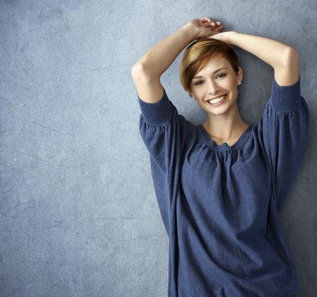 Foto de Happy young woman in blue jeans leaning against wall, smiling - Imagen libre de derechos