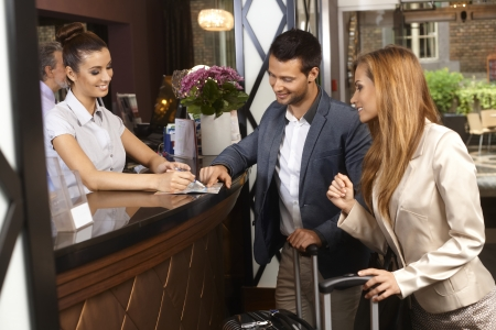 Photo for Receptionist giving tourist information to hotel guests upon arrival. - Royalty Free Image