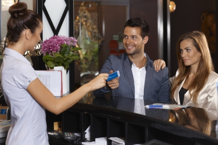 Photo for Receptionist giving key card to new guests at hotel, smiling happy. - Royalty Free Image