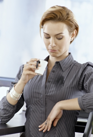 Foto de Young businesswoman looking at stain on her blouse made by spilling coffee on it. - Imagen libre de derechos