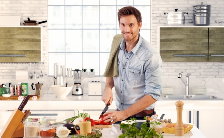 Photo for Happy handsome man cooking in kitchen at home. - Royalty Free Image