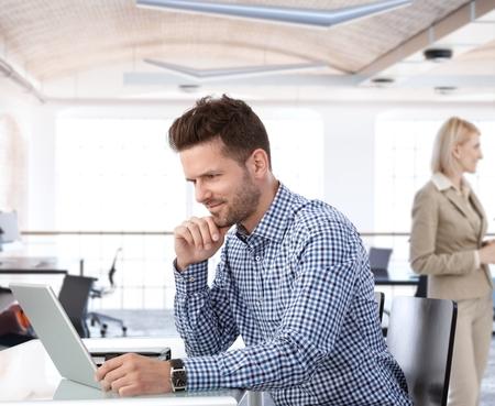 Foto de People working in office, businessman using laptop at desk. - Imagen libre de derechos