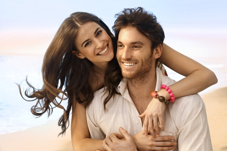 Photo pour Portrait of happy casual caucasian married couple at the beach. Handsome man, attractive young woman, smiling, looking at camera, embracing. - image libre de droit