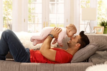 Foto de Young father playing with baby daughter as lying on sofa at home, smiling happy having fun. Side view. - Imagen libre de derechos