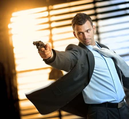 Photo pour Determined caucasian action hero wearing suit and tie holding gun in hand. Standing, moving, aiming with revolver, inspector, cop, police, policeman, indoor, thriller, crime. - image libre de droit
