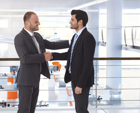Photo for Happy handsome caucasian bristly businessman shaking hands on business deal at office. Hand on shoulder, side view, copyspace, suit. - Royalty Free Image