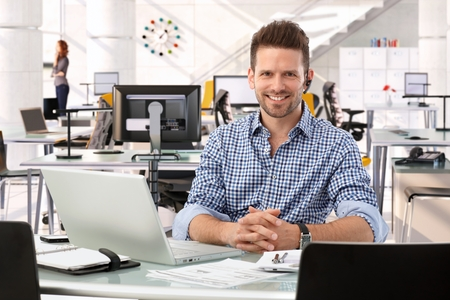 Photo for Happy casual successful caucasian business consultant at startup office, sitting at table with laptop computer, smiling, confident, looking at camera, - Royalty Free Image
