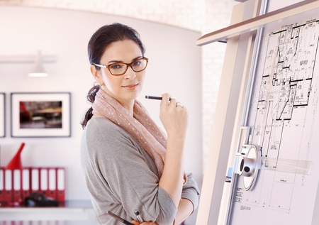 Photo pour Casual female caucasian architect standing at drawing board and floor plan with pencil in hand at office. Wearing glasses, smiling, looking at camera. - image libre de droit